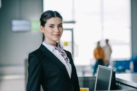 Photo for Attractive young woman smiling at camera while working at check-in desk in airport - Royalty Free Image