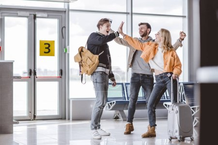 happy young friends giving high five in airport terminal
