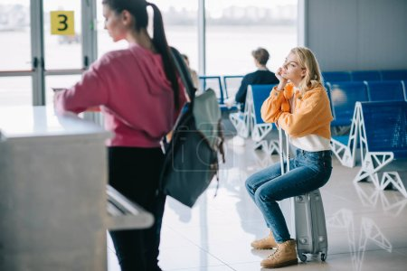 bored young woman sitting on suitcase in airport terminal