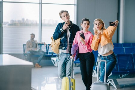 smiling young friends taking selfie with smartphone in airport terminal