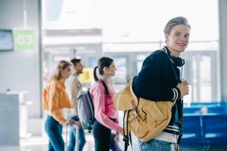 Photo pour Beau jeune homme avec sac à dos, souriant à la caméra lors d'un voyage avec des amis - image libre de droit