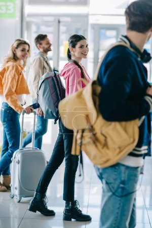 happy young people with luggage in airport terminal