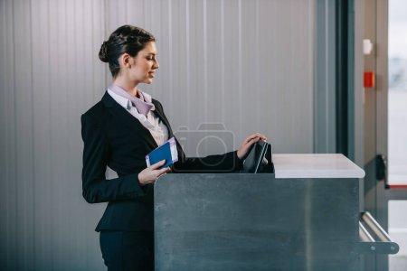 Photo pour Belle jeune travailleuse au comptoir d'enregistrement à l'aéroport - image libre de droit