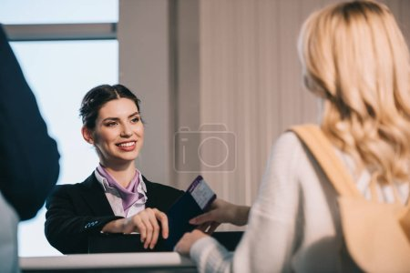cropped shot of airport worker giving passport with boarding pass to young woman at check-in desk