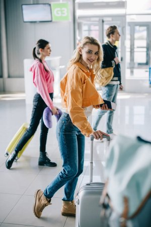 attractive girl with suitcase smiling at camera in airport