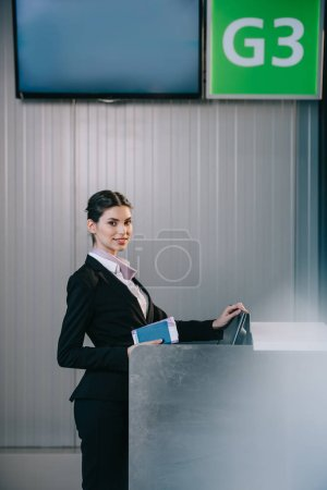 Photo for Beautiful young worker holding documents and smiling at camera at check-in desk in airport - Royalty Free Image