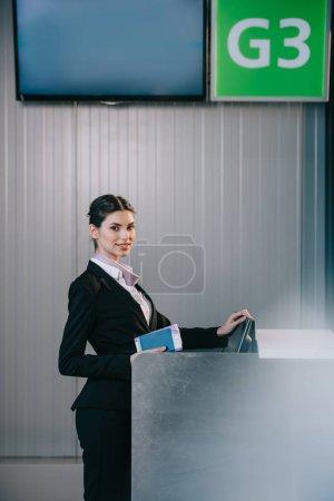 Photo pour Bel jeune travailleur munies de documents et souriant à la caméra au comptoir d'enregistrement à l'aéroport - image libre de droit