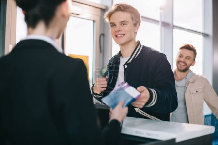 Photo for Cropped shot of smiling young man giving passport to worker at check-in desk in airport - Royalty Free Image