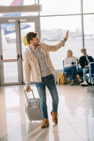 happy young man with suitcase waving hand and looking away in airport