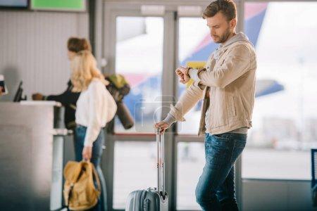 Photo pour Jeune homme avec valise vérifier montre-bracelet à l'aéroport - image libre de droit