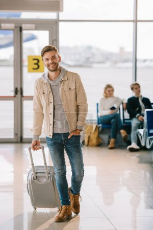 handsome young man with suitcase smiling at camera in airport