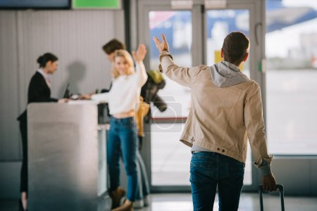 young friends waving hands at check-in desk in airport