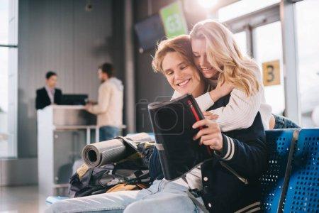 Photo pour Couple jeune heureux hugging en attendant dans le terminal de l'aéroport - image libre de droit
