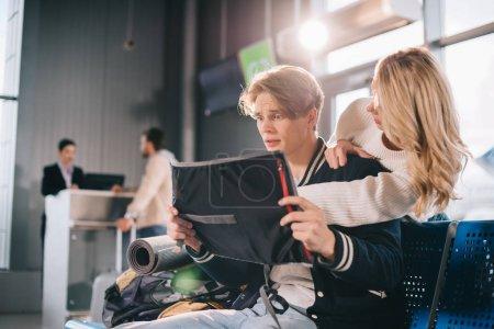 Photo pour Jeune couple à la recherche à la carte et discutant itinéraire dans l'aéroport - image libre de droit