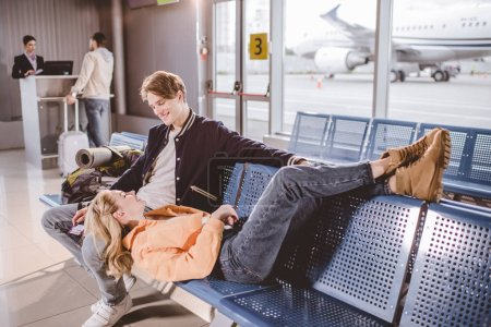 Photo pour Vue d'angle élevé de jeune couple souriant mutuellement pendant que vous attendez de vol à l'aéroport - image libre de droit