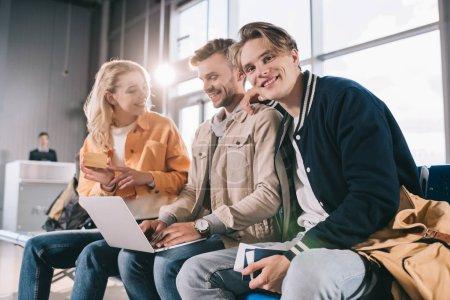 Foto de Amigos felices con tarjeta de crédito y documentos usando la laptop en la terminal del aeropuerto - Imagen libre de derechos
