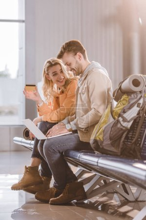 smiling girl holding credit card while man using laptop in airport terminal