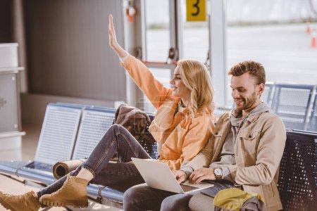 Foto de Sonriente a joven usando laptop y mujer agitando la mano sentado y esperando juntos en aeropuerto - Imagen libre de derechos