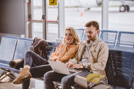 Photo for Young couple of travelers using laptop and waiting for flight in airport terminal - Royalty Free Image