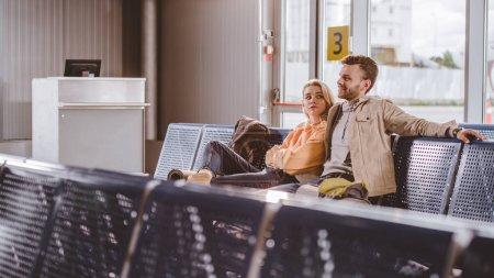 Photo pour Mise au point sélective du jeune couple avec sacs à dos assis ensemble et en attente pour le vol à l'aéroport - image libre de droit
