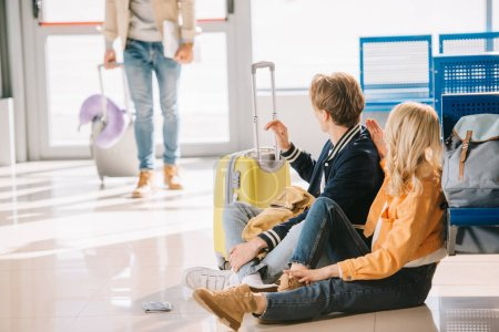 young travelers sitting on floor and looking at friends standing behind in airport