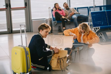 young people looking into backpacks while sitting on floor and waiting for flight in airport