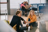 young couple sitting on floor and looking away while waiting for flight in airport