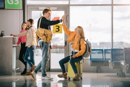 happy young friends giving high five while waiting for flight in airport terminal