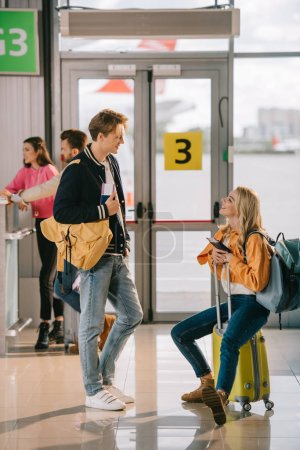 young man and woman with passports and luggage talking in airport terminal
