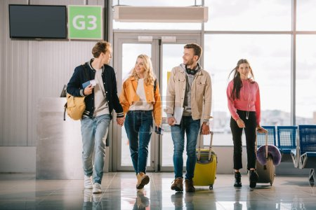 Photo for Smiling young friends with backpacks and suitcases in airport terminal - Royalty Free Image