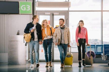 Photo pour Sourire des jeunes amis des documents et des bagages au terminal de l'aéroport - image libre de droit