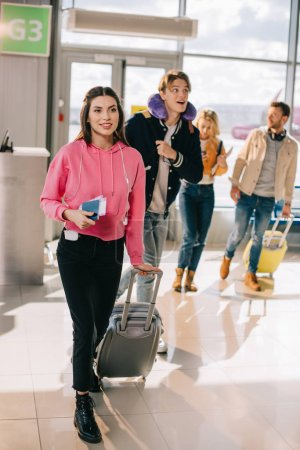 smiling young woman holding suitcase, passport and boarding pass while traveling with friends