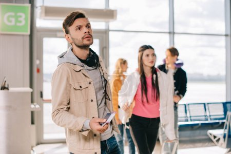 young man holding passport and looking away while traveling with friends in airport