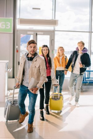 young people with suitcases in airport terminal