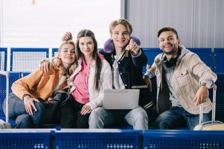 Photo pour Heureux jeunes amis à l'aide d'ordinateur portable et souriant à la caméra pendant que vous attendez de vol dans le terminal de l'aéroport - image libre de droit