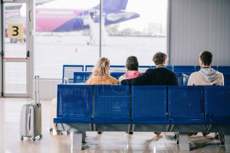 back view of young people sitting and waiting for flight in airport terminal