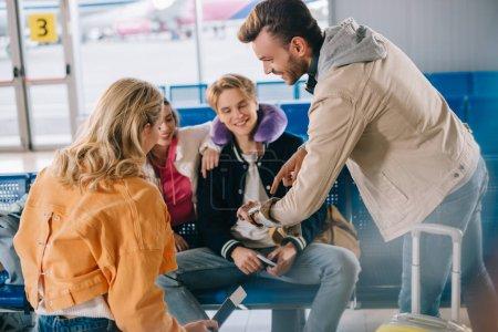 Photo pour Jeunes souriants vérifier montre-bracelet en attendant le vol à l'aéroport - image libre de droit