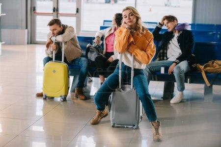 jeunes s'ennuyer avec des bagages en attente pour le vol dans le terminal de l'aéroport
