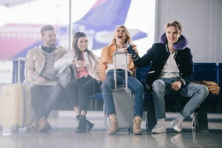 Photo for Young people talking and laughing while waiting in airport terminal - Royalty Free Image