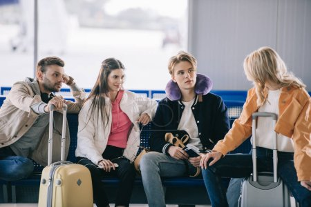 young friends talking while waiting in airport terminal