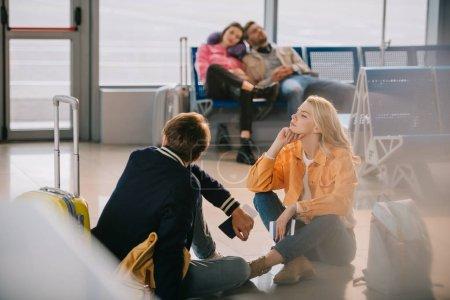 jeunes avec des bagages en attente dans le terminal de l'aéroport