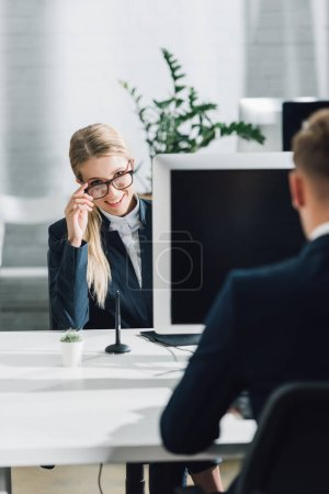cropped shot of young businessman and smiling businesswoman in eyeglasses working in open space office