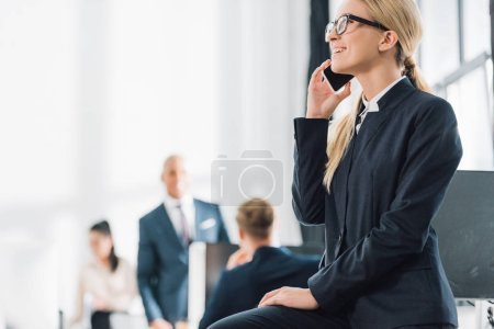 smiling young businesswoman in eyeglasses talking by smartphone and looking away in open space office