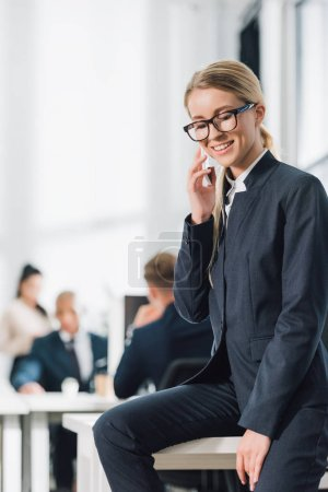 Photo for Smiling young businesswoman in eyeglasses talking by smartphone and looking down in office - Royalty Free Image