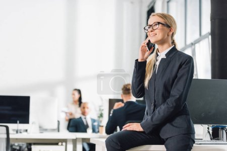 smiling young businesswoman in eyeglasses talking by smartphone and looking away in office