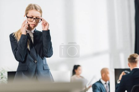 Photo for Focused young businesswoman talking by smartphone and adjusting eyeglasses in office - Royalty Free Image