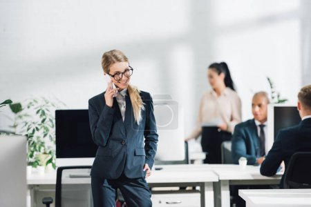 Photo for Smiling young businesswoman in eyeglasses talking by smartphone and looking at camera while working with colleagues in open space office - Royalty Free Image
