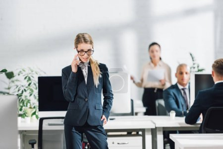attractive young businesswoman in eyeglasses talking by smartphone and looking at camera while working with colleagues in open space office