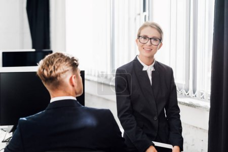 young businessman and businesswoman in formal wear working together in open space office