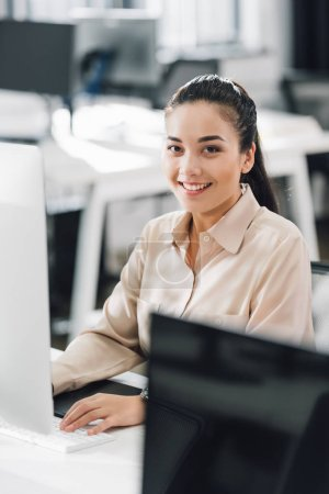 Photo for Beautiful young businesswoman using desktop computer and smiling at camera in office - Royalty Free Image
